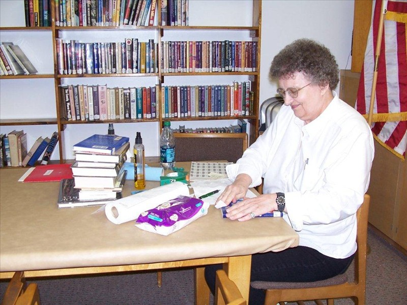 Penny Russell spends many hours volunteering at the Burley Public Library. Here she is bar-coding books.